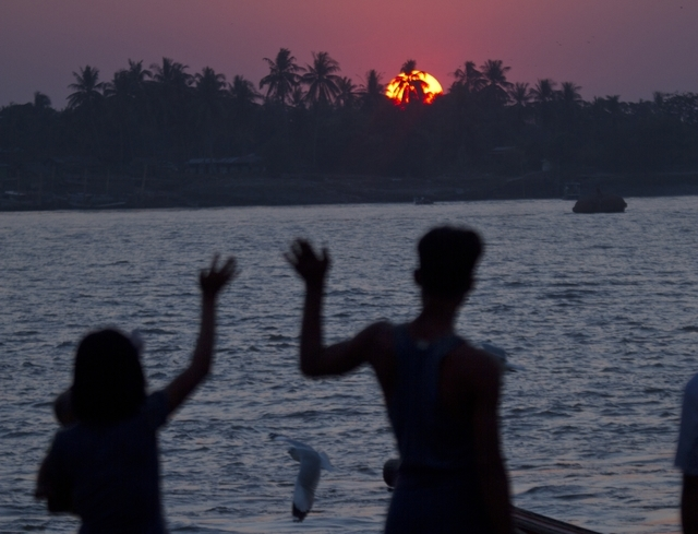 A couple waves during the last sunset of the year at a jetty at Yangon river in Yangon, Myanmar Wednesday, Dec. 31, 2014. (AP Photo/Khin Maung Win)