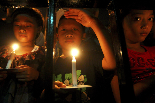 Indonesian children hold candles to pray for the victims of AirAsia Flight 8501 in Surabaya, Indonesia, Wednesday, Dec. 31, 2014. Bad weather hindered efforts to recover victims of the jet on Wedn ...