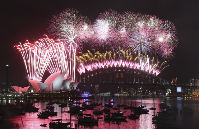 Fireworks explode over the Opera House and the Harbour Bridge during New Years Eve  celebrations in Sydney, Australia, Thursday, Jan. 1, 2015. Thousands of people crammed into Lady Macquaries Chai ...