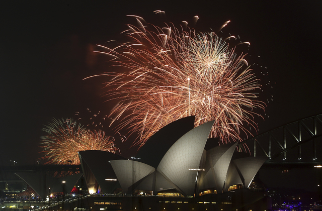 Fireworks explode over the Opera House and the Harbour Bridge during New Years Eve celebrations in Sydney, Australia, Wednesday, Dec. 31, 2014. Thousands of people crammed into Lady Macquaries Cha ...