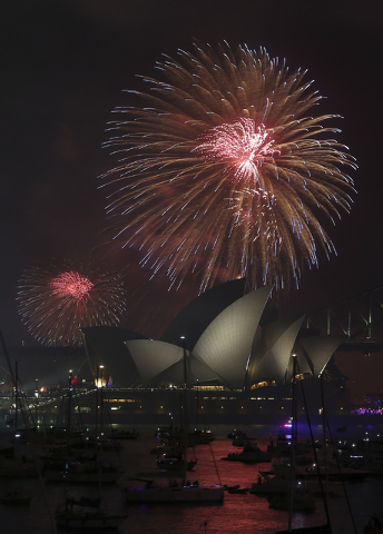 Fireworks explode over the Opera House and the Harbour Bridge during New Year's Eve celebrations in Sydney, Australia, Wednesday, Dec. 31, 2014. Thousands of people crammed into Lady Macquaries Ch ...