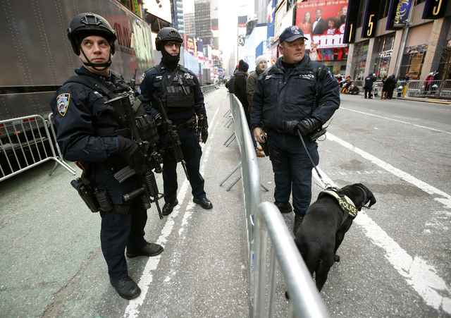 New York city police officers armed with heavy weapons pause for a break in between patrolling Times Square on New Year's Eve in New York, Wednesday, Dec. 31, 2014.  (AP Photo/Kathy Willens)