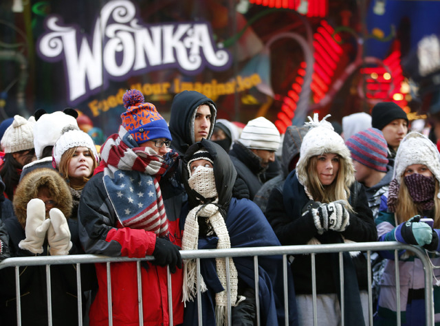 Revelers dressed for expected 20 degree temperatures line a barricade in Times Square hours before the celebration was set to begin on New Years Eve in New York, Wednesday, Dec. 31, 2014.  (AP Pho ...