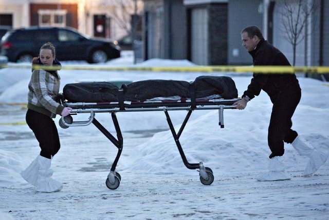 The body of a victim is carried out of a north Edmonton home in Edmonton, Alberta, Tuesday, Dec. 30, 2014. Nine people, including seven adults and two young children, were found dead at three sepa ...