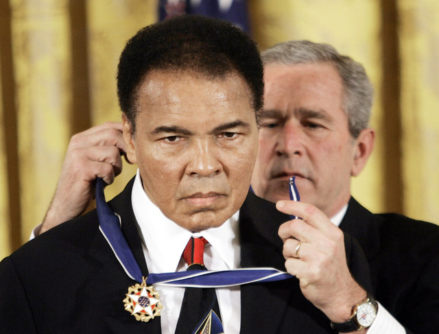 In this Nov. 9, 2005 file photo, President Bush presents the Presidential Medal of Freedom to boxer Muhammad Ali in the East Room of the White House. He is now so much a part of the nation's socia ...