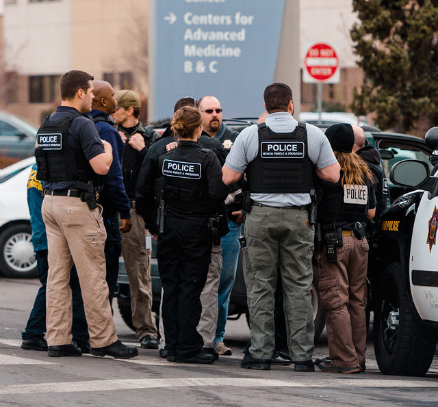 Officers gather in front of Renown Regional Medical Center on Tuesday in Reno after a gunman shot and killed a doctor and wounded two people before killing himself. (AP Photo/Scott Sady)