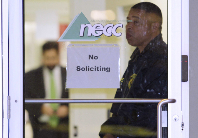 A Food and Drug Administration Agent stands at the doorway of New England Compounding Center in Framingham, Massachusetts, Oct. 16, 2012. Two co-founders and 12 other former employees of the compa ...
