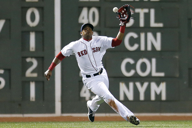 Boston Red Sox's Yoenis Cespedes misplays the fly ball by Baltimore Orioles' Adam Jones allowing a run to score during the seventh inning of a baseball game in Boston, Monday, Sept. 8, 2014. (AP P ...