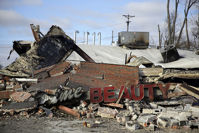 A building burned to the ground is shown Tuesday, Nov. 25, 2014, in Dellwood, Mo. The building and several others in and around Ferguson were burned during protests after a grand jury decided not  ...