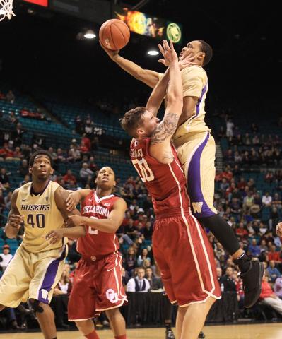 Washington guard Darin Johnson fouls Oklahoma forward Ryan Spangler while taking a shot during their MGM Grand Showcase game Saturday, Dec. 20, 2014. (Sam Morris/Las Vegas Review-Journal)