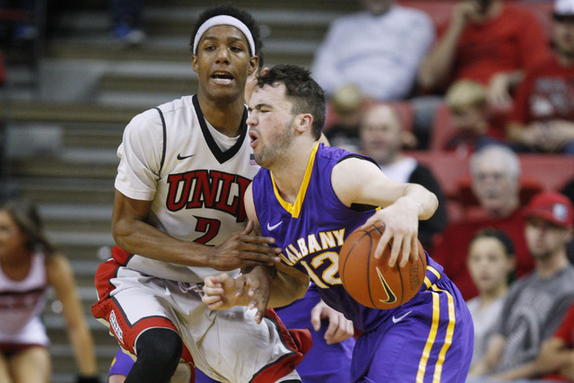 UNLV guard Patrick McCaw fouls Albany guard Peter Hooley during their game Saturday, Nov. 29, 2014 at the Thomas & Mack Center. (Sam Morris/Las Vegas Review-Journal)