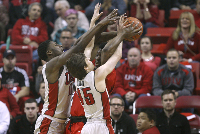 UNLV forward Goodluck Okonoboh  and UNLV guard Cody Doolin force a held ball situation with Arizona forward Stanley Johnson during their game Tuesday, Dec. 23, 2014 at the Thomas & Mack Center. (S ...