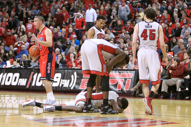 UNLV forward Dwayne Morgan lies on the floor after taking an elbow to the head from Arizona center Kaleb Tarczewski during their game Tuesday, Dec. 23, 2014 at the Thomas & Mack Center. (Sam Morri ...