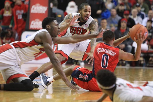 UNLV forward Goodluck Okonoboh, left, and UNLV guard Jelan Kendrick try to get a loose ball from Arizona guard Parker Jackson-Cartwright during their game Tuesday, Dec. 23, 2014 at the Thomas & Ma ...