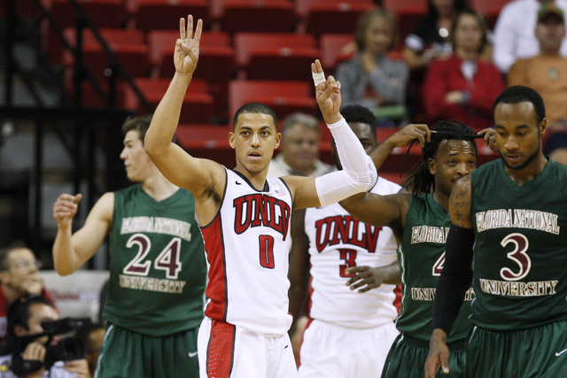 UNLV guard Kendall Smith checks with his coaches about what play to run against Florida National University during their exhibition game Wednesday, Nov. 5, 2014 at the Thomas & Mack Center in Las  ...