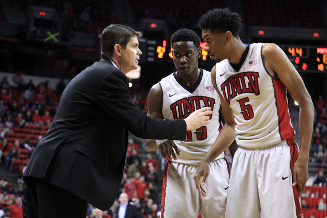 UNLV head coach talks to UNLV forward Dwayne Morgan, center, and UNLV forward Christian Wood  during the second half of their game Wednesday, Dec. 17, 2014 at the Thomas & Mack Center. UNLV won 75 ...