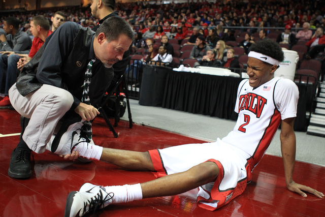 Trainer Dave Tomchek works out a cramp in UNLV guard Patrick McCaw's leg during their game against Saint Katherine Friday, Dec. 5, 2014 at the Orleans Arena. UNLV won the game 113-53. (Sam Morris/ ...