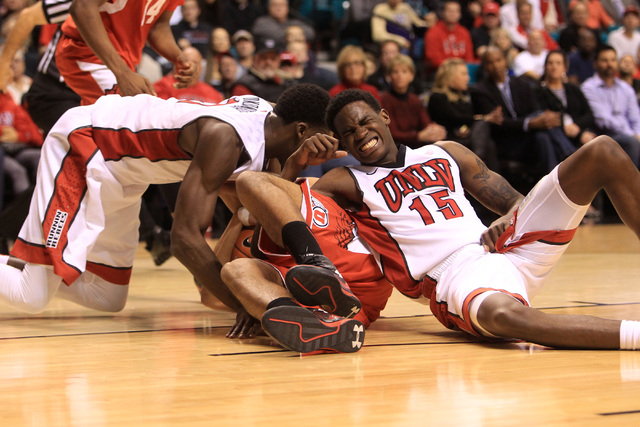 UNLV forward Goodluck Okonoboh, left, and UNLV forward Dwayne Morgan hit the ground while fighting for a loose ball with Utah forward Chris Reyes during their MGM Grand Showcase game Saturday, Dec ...