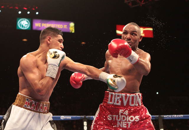 Amir Khan, left lands a blow to Devon Alexander during the title bout for the WBC Silver welterweight fight at the MGM Grand Garden in Las Vegas, Friday, Dec. 13, 2014. (Donavon Lockett/Las Vegas  ...