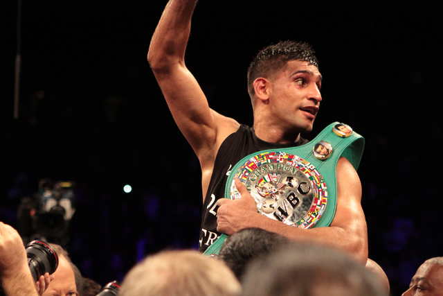 Amir Khan waves to the crowd while being hoisted on the shoulders of his boxing crew after winning the title bout against Devon Alexander for the WBC Silver welterweight fight at the MGM Grand Gar ...