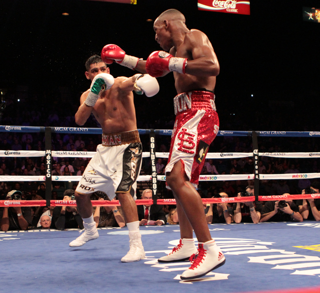 Devon Alexander, foreground works to counter a punch from Amir Khan during their title bout for the WBC Silver welterweight fight at the MGM Grand Garden in Las Vegas, Friday, Dec. 13, 2014. (Dona ...