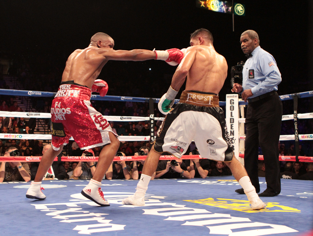 Devon Alexander, left, throws a punch to Amir Khan while the Referee, Robert Byrd watches intently, during the title bout for the WBC Silver welterweight fight at the MGM Grand Garden in Las Vegas ...