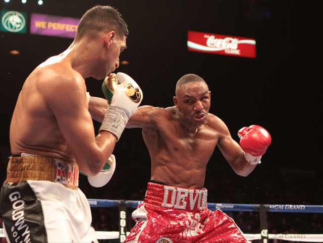 Amir Khan, left, prepares for a punch incoming from Devon Alexander during the title bout for the WBC Silver welterweight fight at the MGM Grand Garden in Las Vegas, Friday, Dec. 13, 2014. (Donavo ...