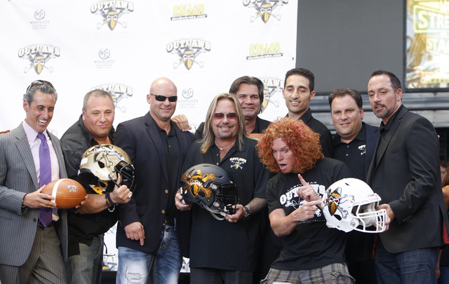 Vince Neil, owner of Las Vegas' new Arena Football League team, the Las Vegas Outlaws, poses for photos with his management team and Carrot Top Thursday, Sept. 25, 2014 at the Fremont Street Exper ...