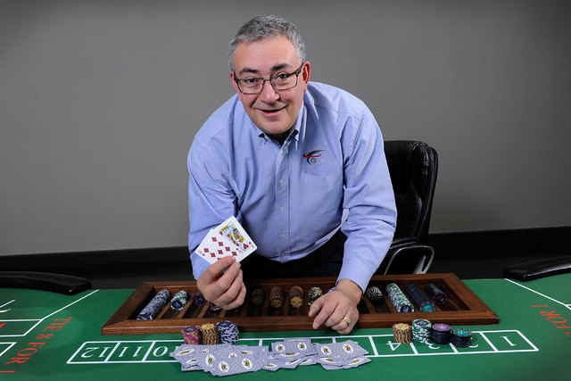 eConnect President and CEO Henry Valentino poses at a baccarat table in his Las Vegas office on Monday, Nov. 24, 2014. Valentino developed software that allows companies to analyze customer behavi ...
