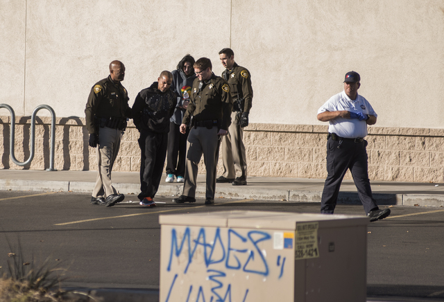 Las Vegas Police secures the man suspected of a string of robberies, second from left, after officers stopped the suspect's vehicle shortly after 5 a.m. from the corner of Desert Inn and Fort Apac ...