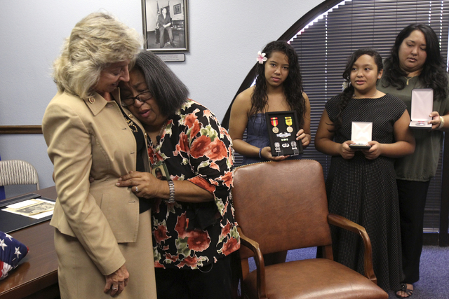 Johnnette Fafard, widow of Army Sgt. Raymond Fafard, second from left, hugs Rep. Dina Titus during an award ceremony honoring her husband at Titus' Las Vegas office Tuesday, Sep. 3, 2013. Fafard d ...