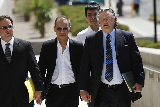 Paul Phua, second from left, and his son Darren, third from left, walk to Lloyd George Federal Courthouse in Las Vegas with their attorneys Richard Schonfeld, left, and David Chesnoff, for their a ...