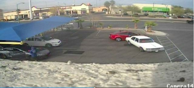 A white car is shown as it backs up in a car wash parking lot in this image from a YouTube video. A man was hit and injured. (Courtesy, YouTube)