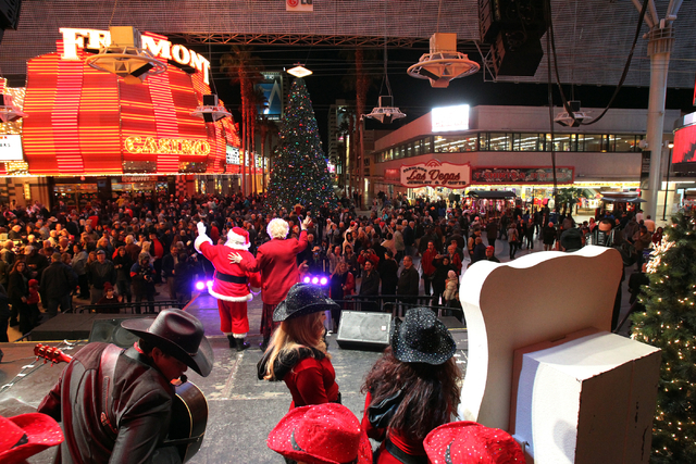 Las Vegas Mayor Carolyn G. Goodman, right, and Santa Claus, also known as Bob Dempsey, wave to the crowd after lighting the official Las Vegas Christmas tree at the Fremont Street Experience 3rd S ...