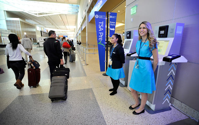 Clear ambassadors Luz Vargas, left, and Alyssa Ramos stand near a Clear airport security kiosk at McCarran International Airport on Tuesday, Dec. 9, 2014, in Las Vegas. The Clear service allows pa ...