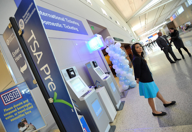 Clear ambassador Kira Tommori stands near a Clear airport security kiosk at McCarran International Airport on Tuesday, Dec. 9, 2014, in Las Vegas. The Clear service allows passengers to skip to th ...