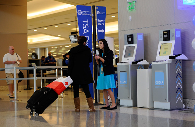 Clear ambassador Kira Tommori assists a passenger near a Clear airport security kiosk at McCarran International Airport on Tuesday, Dec. 9, 2014, in Las Vegas. The Clear service allows passengers  ...
