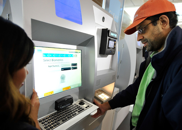 Passenger Ajay Gupta, right, has his finger prints scanned with the assistance of Clear ambassador Antionette Serrano at a Clear airport security kiosk as he signs up for the service at McCarran I ...