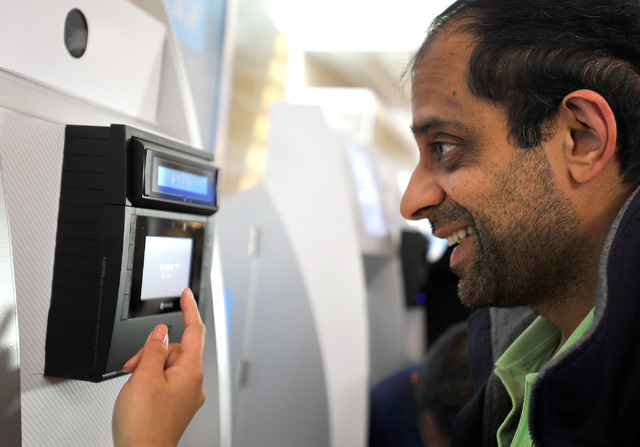 Passenger Ajay Gupta has his eyes scanned at a Clear airport security kiosk as he signs up for the service at McCarran International Airport on Tuesday, Dec. 9, 2014, in Las Vegas. The service all ...