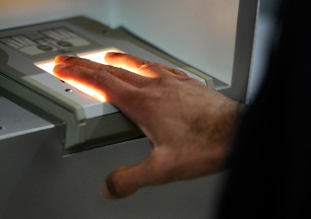 Ajay Gupta has his finger prints scanned at a Clear airport security kiosk as he signs up for the service at McCarran International Airport on Tuesday, Dec. 9, 2014, in Las Vegas. The service allo ...
