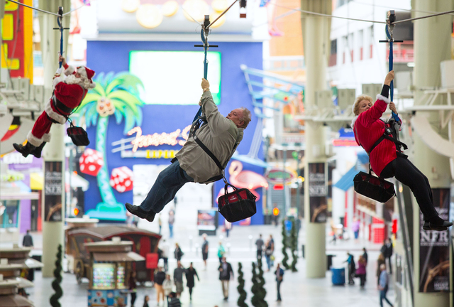 Riding down the SlotZilla zip line at Fremont Street Experience are, from left, Santa Claus, Robin Leach and Las Vegas Mayor Carolyn Goodman on Tuesday, Dec. 2, 2014. (Samantha Clemens-Kerbs/Las V ...