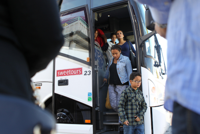 Children unload a tour bus at Circus Circus Adventure Dome in Las Vegas for an event hosted by St. Jude's Ranch for Children Sunday, Dec. 14, 2014. Nearly 100 foster children separated from their  ...