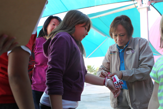 Catalina, left, 10, receives a wristband from ride attendant Jocelyn Bautista during an event hosted by St. Jude's Ranch for Children at Circus Circus Adventure Dome in Las Vegas Sunday, Dec. 14,  ...