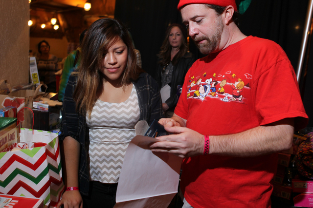 Ana Aviles, left, 18, gets help from Kevin Nelson, St. Jude volunteer, as she shops for a free gift for her younger brother during an event hosted by St. Jude's Ranch for Children at Circus Circus ...