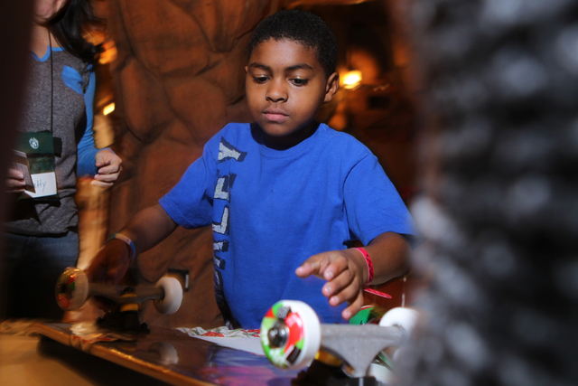Seven, 11, waits to get a skateboard gift wrapped for his brother during an event hosted by St. Jude's Ranch for Children at Circus Circus Adventure Dome in Las Vegas Sunday, Dec. 14, 2014. Nearly ...