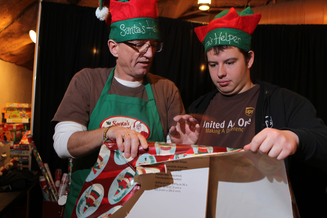 Volunteers with St. Jude's Ranch for Children Ed McCay, left, and his son Joshua, 18, gift wrap presents for children during their visit to Circus Circus Adventure Dome in Las Vegas Sunday, Dec. 1 ...