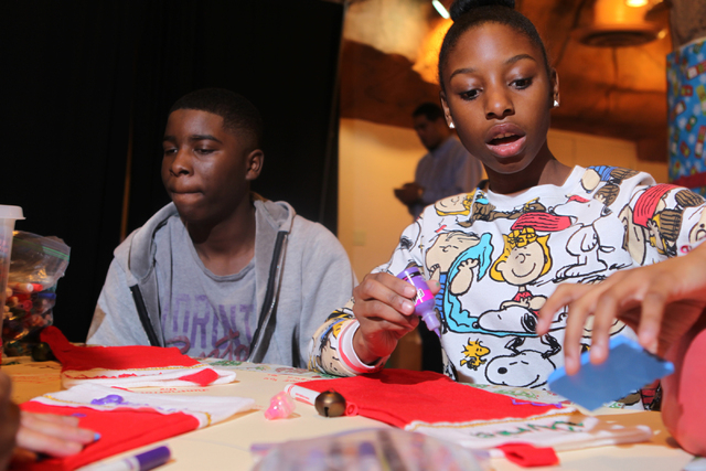 Jumarion, left, 13, and his sister Junia, 16, decorate Christmas Stockings during an event hosted by St. Jude's Ranch for Children at Circus Circus Adventure Dome in Las Vegas Sunday, Dec. 14, 201 ...