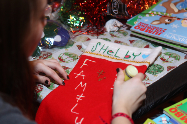 Kayla, 15, decorates a Christmas Stocking for her older sister during an event hosted by St. Jude's Ranch for Children at Circus Circus Adventure Dome in Las Vegas Sunday, Dec. 14, 2014. Nearly 10 ...