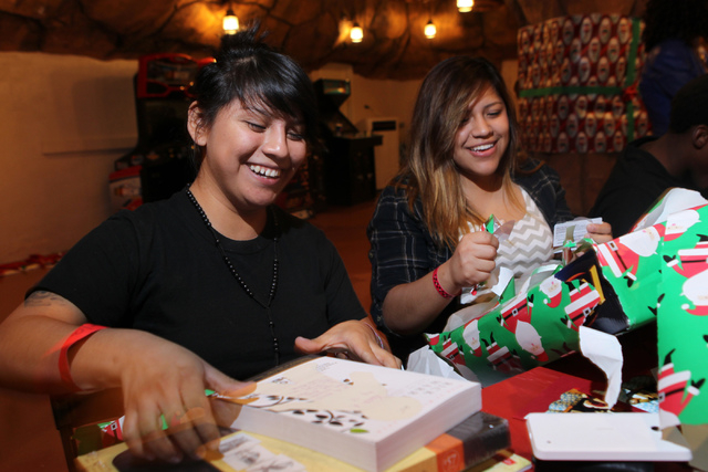 Karla Aviles, left, 19, and her sister Ana, 18, open Christmas gifts that they exchanged with each other during an event hosted by St. Jude's Ranch for Children at Circus Circus Adventure Dome in  ...