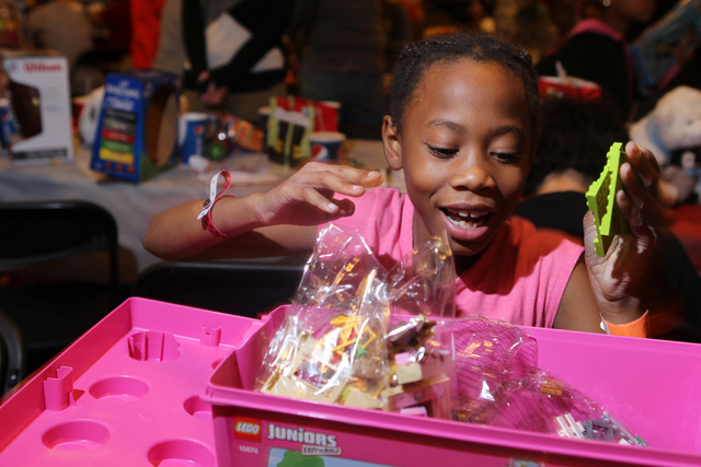 Janaiah, 9, opens a Lego box she received as a Christmas gift during an event hosted by St. Jude's Ranch for Children at Circus Circus Adventure Dome in Las Vegas Sunday, Dec. 14, 2014. Nearly 100 ...